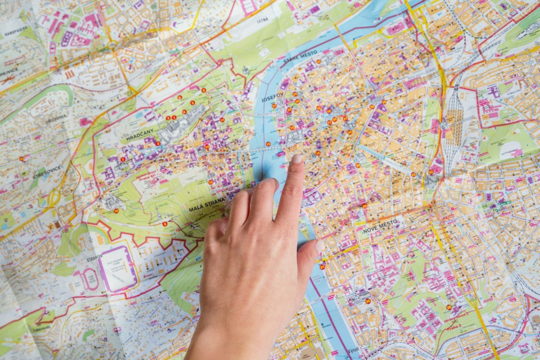 finger pointing a location on a map