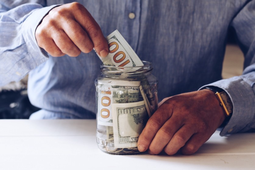 adding dollars into a glass jar