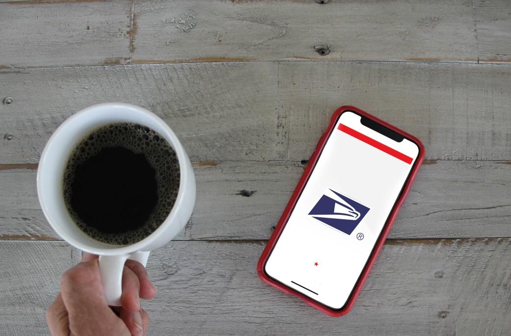 usps website on a phone next to a coffee mug