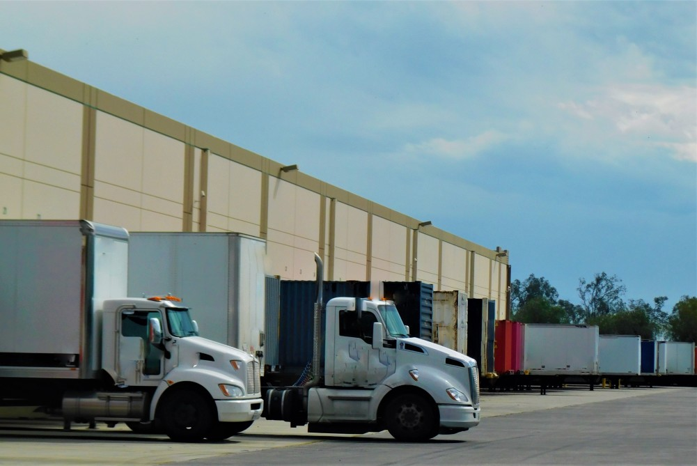 trucks in front of a usps distribution center